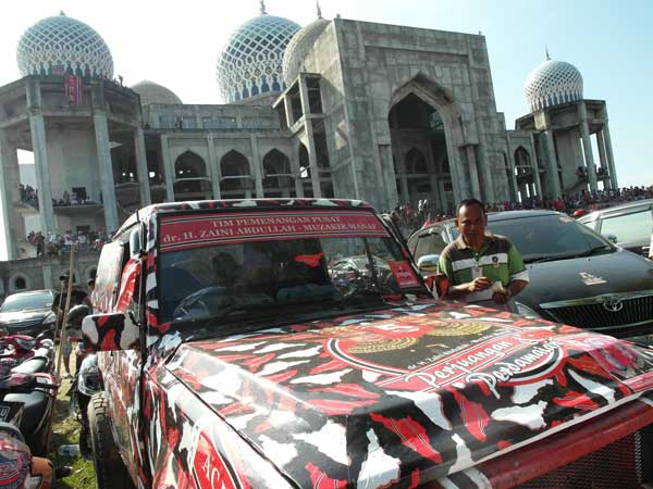 A proto-military jeep in front of a mosque at a Partai Aceh rally in Aceh, Indonesia